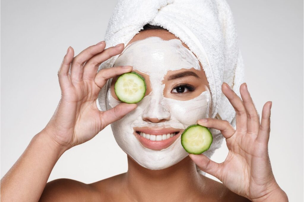 A woman with a mask on her face while holding slices of cucumber
