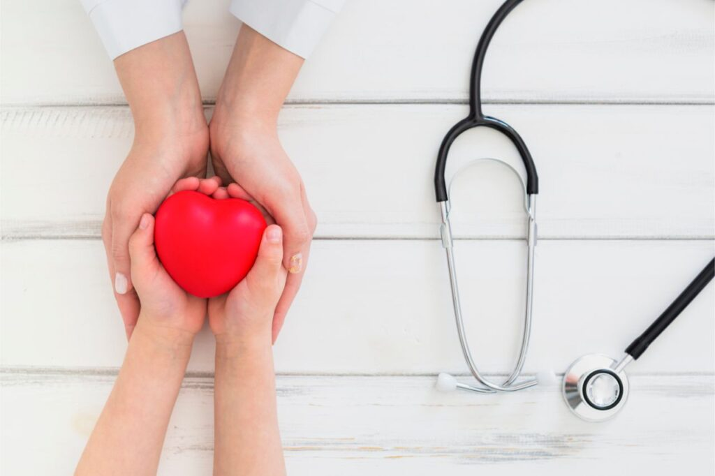 Photo of a doctor and a woman holding a heart